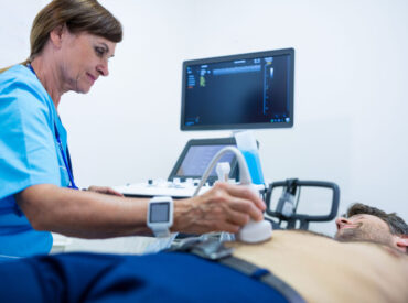 Man getting ultrasound of a abdomen from doctor in hospital