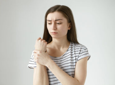 Studio shot of sad frustrated young woman in striped top frowning, holding hand on her aching wrist, massaging pain area, having painful facial expression, suffering from joint pain, arthritis or gout